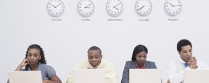 Business men and women using laptops in office with clocks on wall