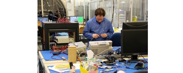 (Image: Anthony Reinhart, Communitech). An employee at the UTIAS Space Flight Laboratory in Toronto assembles a sa
