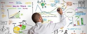 Man drawing marketing metrics on a whiteboard.