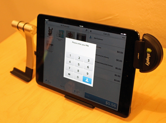 Shopify's credit card dongle on an iPad mini, with an iPad stand.