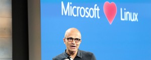 "Microsoft CEO Satya Nadella appears in front of a ""Microsoft loves Linux"" projection."
